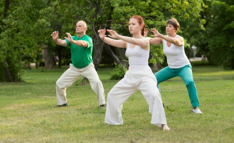 Groupe de trois personnes en pleine séance de tai chi