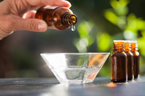 main déversant de l'huile essentielle dans un bol