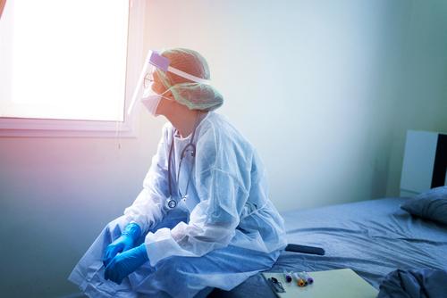 medecin assise sur lit d'hopital regardant au loin