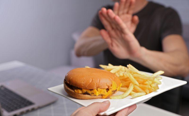 Homme refusant de manger de la nourriture trop grasse