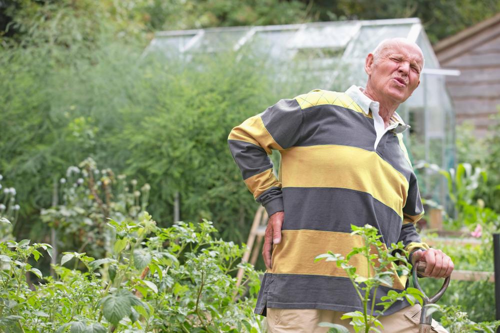 Homme souffrant de maux de dos dans son jardin