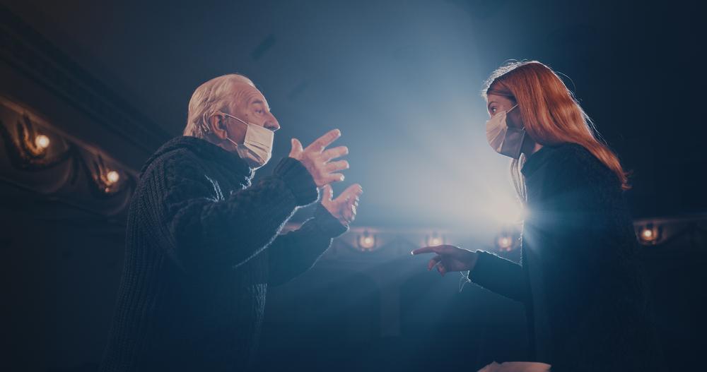scene de théâtre deux personne se disputent avec un masque
