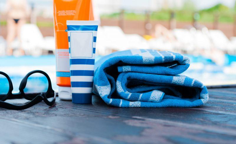 cremes solaires sur un ponton à la plage avec lunettes de soleil et serviette