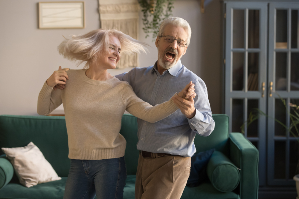 couple de sénior dansant dans leur salon
