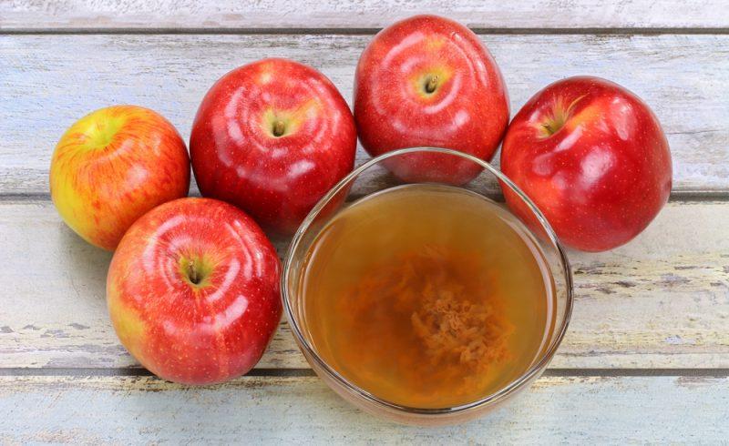 Pommes fraîches et un bol de vinaigre de cidre de pomme et non filtré
